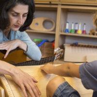 Musikkterapeut Karin Mössler utforsker instrumentet sammen med barnet.
